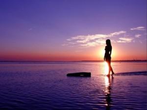 Una-mujer-camina-por-la-orilla-del-mar-al-atardecer